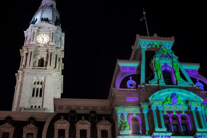 The facade of City Hall is lit by spotlights for the Christmas season. (Brad Larrison for WHYY)