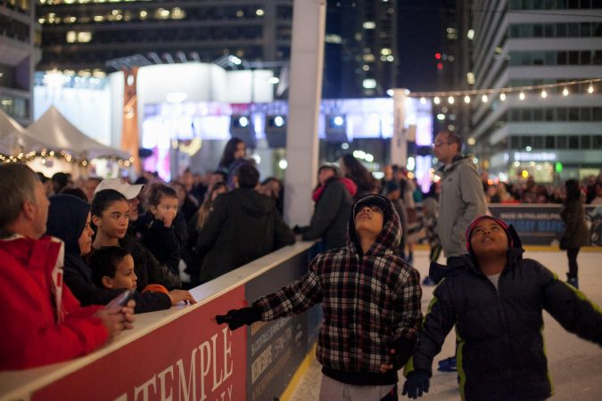 Young ice skaters look up at City Hall while gliding around the Dilworth Park skating rink. (Brad Larrison for WHYY)