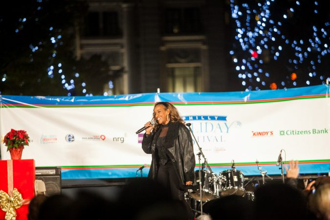 Singer Kathy Sledge performs at the Christmas tree lighting ceremony outside of City Hall Friday. (Brad Larrison for WHYY)