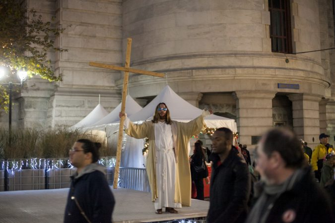 The man who calls himself Philly Jesus quotes scripture in the City Hall courtyard before the Christmas tree lighting ceremony Friday evening. (Brad Larrison for WHYY)