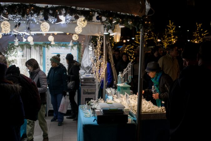 Shoppers browse a stand at the Christmas Village in Dilworth Park Friday evening. (Brad Larrison for WHYY)