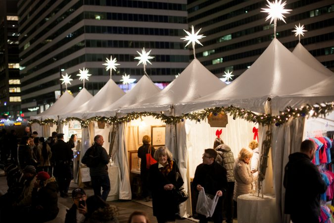 Shoppers browse stands at the Christmas Village in Dilworth Park Friday evening. (Brad Larrison for WHYY)