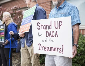 Community members held signs in support of a DREAM act and DACA recipients outside Rep. Glenn Thompson's Centre County office in September. (Min Xian/Keystone Crossroads)