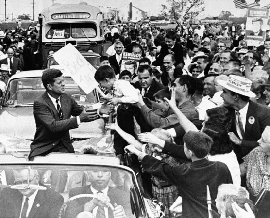 Sen. John F. Kennedy, democratic presidential nominee, reaches out for unidentified youngster held out be enthusiastic father as the senatorís motorcade moved through out cheering crowd at Levittown, NJ., Oct. 16, 1960 this afternoon. Kennedy address throng officially estimated at 20,000 in Levittown, shopping plaza. The crowd interrupted Kennedyís speech with applause when he said he had disagreements with Vice President Nixon. (AP Photo)