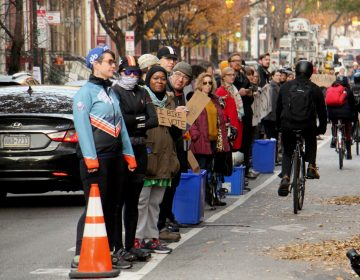 Protesters demanding protected bike lanes form a human barrier on Nov. 28, stretching for two blocks along Spruce Street near 11th Street, where a cyclist was killed by a garbage truck the previous morning. (Emma Lee/WHYY)