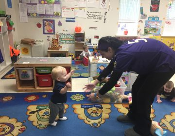 A teacher at Babes on the Square, which is a Star 4 program,  works with toddlers  (Cris Barrish/WHYY)
