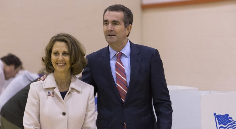 Democratic gubernatorial candidate Lt. Gov. Ralph Northam, right, and his wife, Pam, carry their ballots to the tally machine in Norfolk, Va.