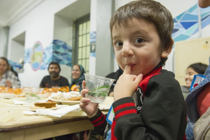 Hasib licks his fingers during the Annual Thanksgiving Celebration dinner. (Jonathan Wilson for WHYY)