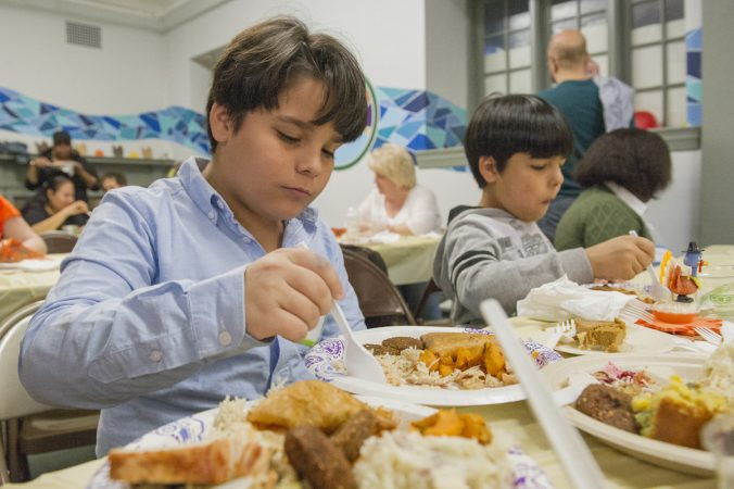 Iraqi refugees Ali, left and his brother Hayder enjoy their Thanksgiving dinner. (Jonathan Wilson for WHYY)