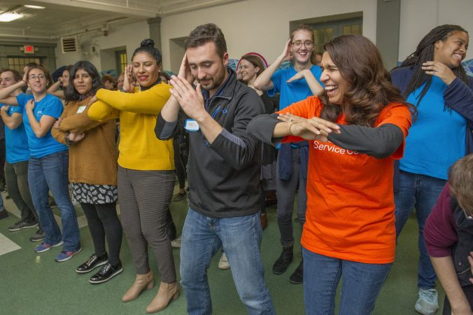 Volunteer Brenda Gorski, right leads refugees and volunteers in the Macarena. (Jonathan Wilson for WHYY)