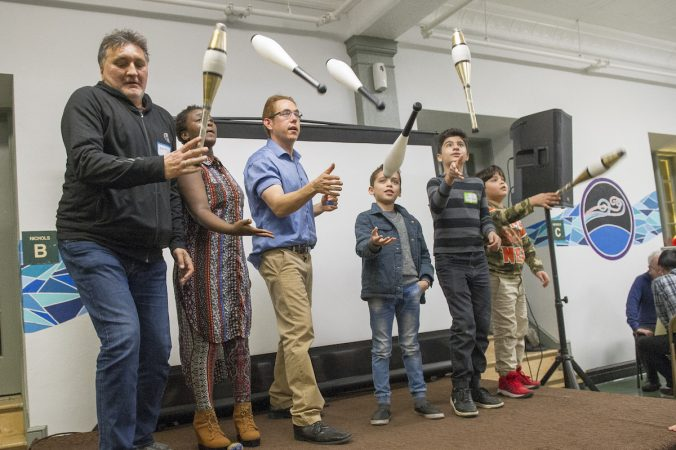 Ben Edoff, third from left, teaches refugees how to juggle. (Jonathan Wilson for WHYY)