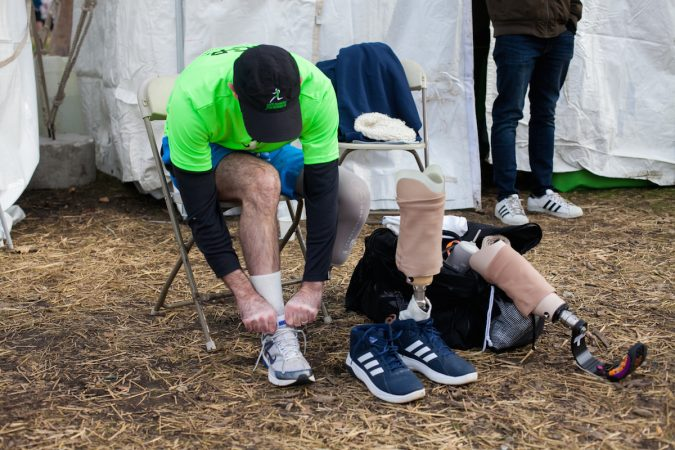 Evan Freiberg changes his shoe and his prosthetic before the Rothman Institute 8k Saturday. The 43-year-old is diagnosed with leiomyosarcoma, a form of cancer, and competed after losing the bottom portion of his left leg to the disease. (Brad Larrison for WHYY)