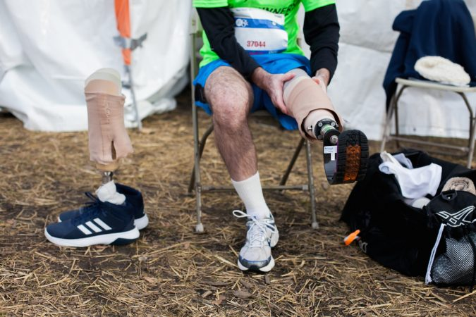 Evan Freiberg finishes putting on his running prosthetic before the Rothman Institute 8k Saturday. The 43-year-old is diagnosed with leiomyosarcoma, a form of cancer, and competed after losing the bottom portion of his left leg to the disease. (Brad Larrison for WHYY)
