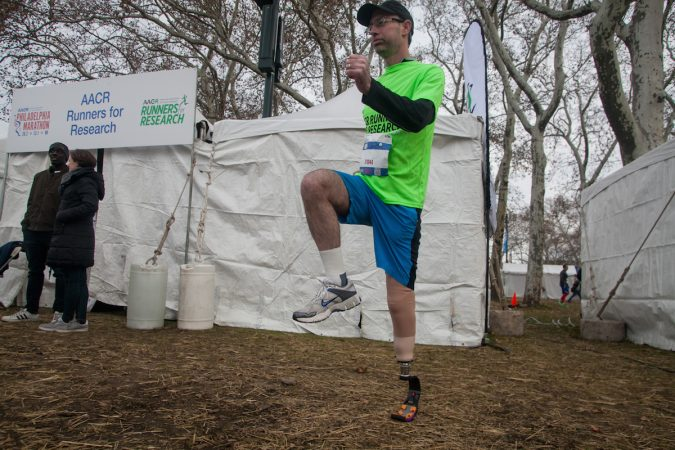 Evan Freiberg warms up before the Rothman Institute 8k Saturday. The 43-year-old is diagnosed with leiomyosarcoma, a form of cancer, and competed after losing the bottom portion of his left leg to the disease. (Brad Larrison for WHYY)