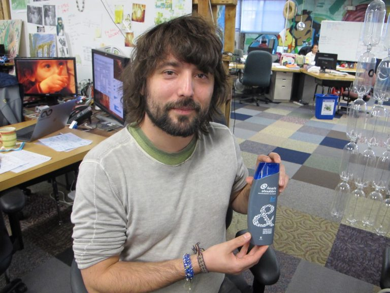 TerraCycle CEO Tom Szaky shows a shampoo bottle made with recycled plastic collected from beaches and oceans. (Phil Gregory/WHYY)