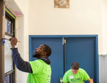 Andre Wright paints puts a new coat of paint on a window frame in the Sharswwod Athletic Rec Center. (