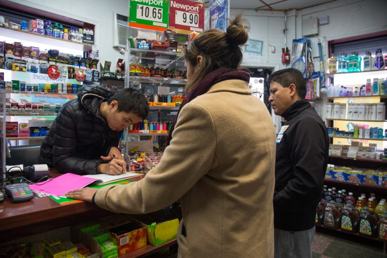 Gerardo Aguillon Castro (right) and Alana Adams, left, canvass businesses and homes in South Philadelphia as part of a