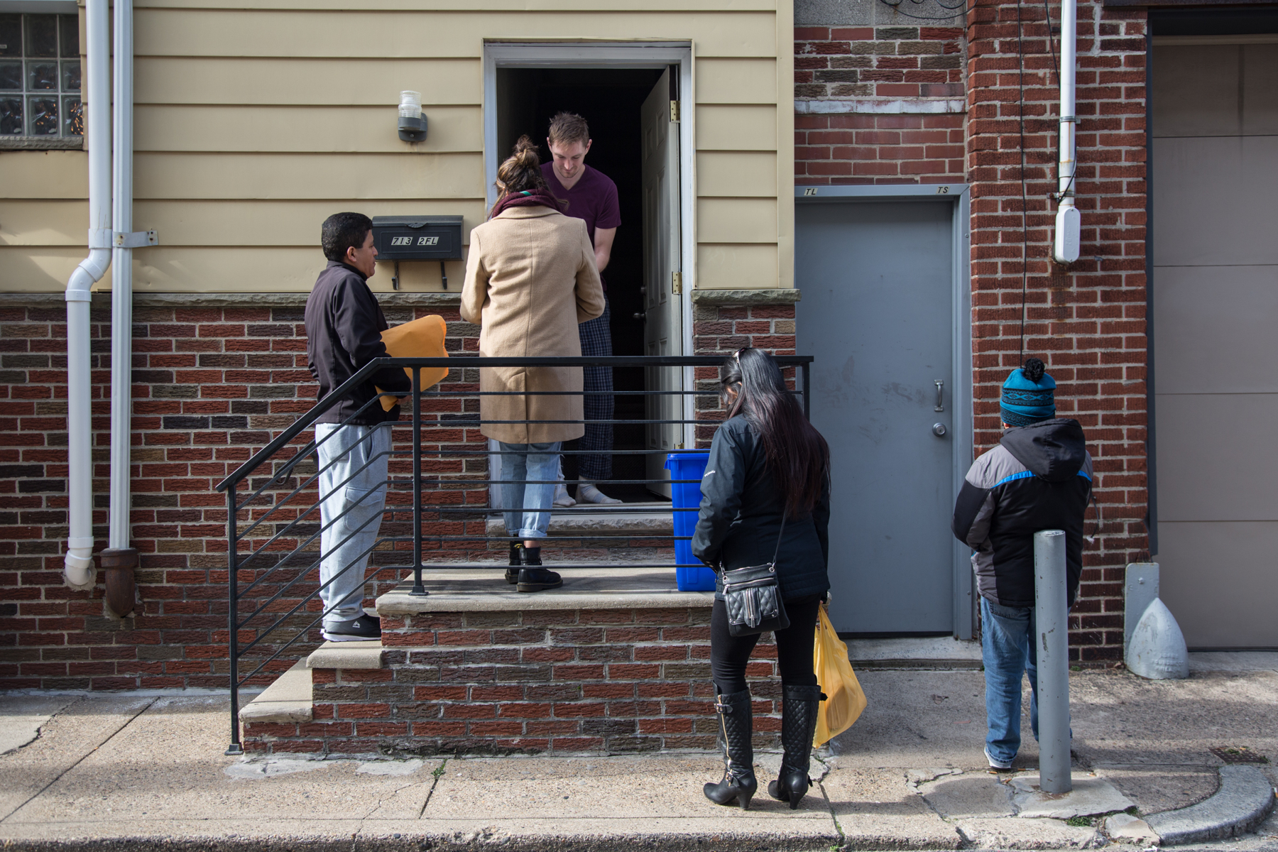 A group of people hand out literature to a man at the door of a South Philadelphia row home