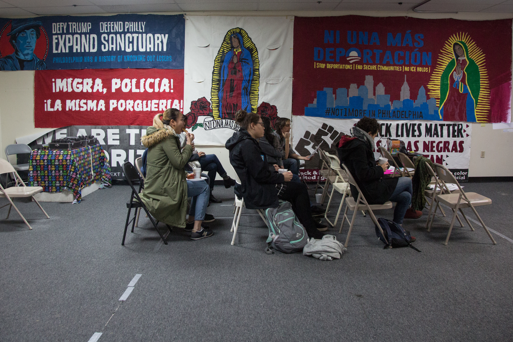 People in winter coats sit on folding chairs against a background of colorful posters in Spanish language
