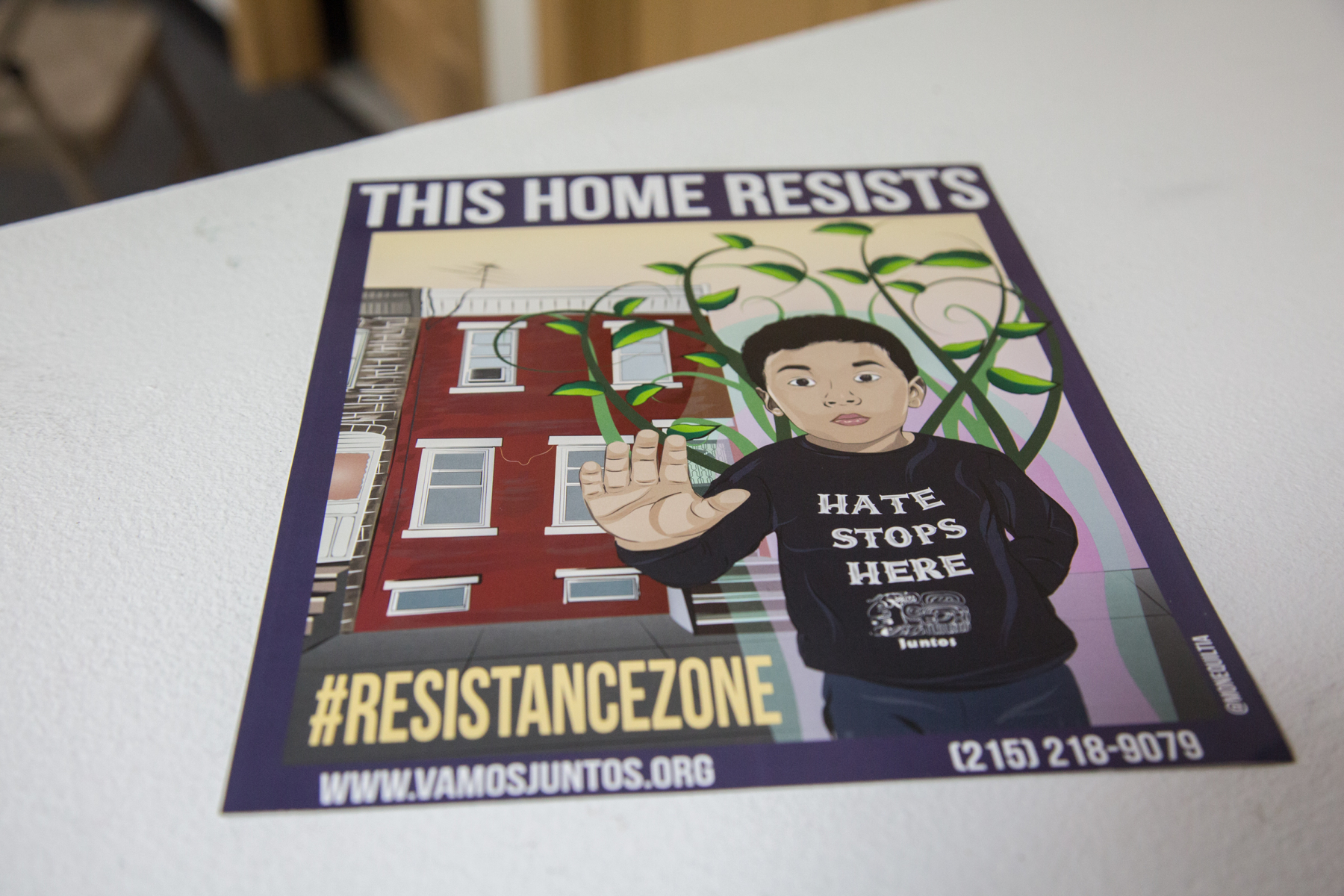 "A poster shows a boy standing in front of a rowhome with his hand held up palm out. Across the top it says ""this home resists."""