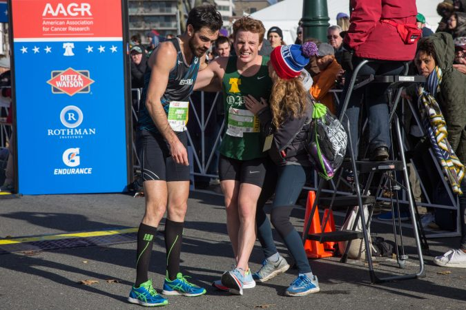 Patrick Richie, 26, center, is helped by his friend Liz Pagonis, and fellow runner, Johan Trimaille, after being the first Philadelphian to cross the finish line at the 23rd annual Philadelphia Marathon on Sunday, November 19th, 2017.