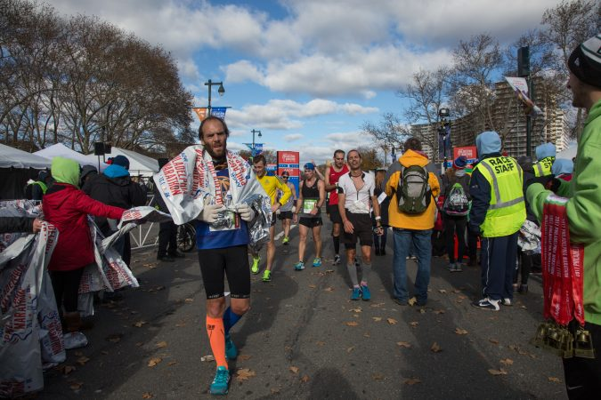 Racers walk for the first time in over two hours as they cross the finish line at the 23rd annual Philadelphia Marathon on Sunday November 19th, 2017.
