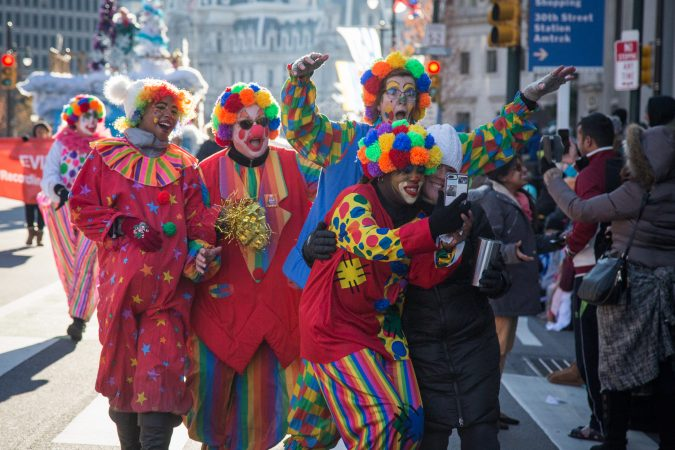 Clowns marching in the parade take a selfie with a spectator at the 98th annual Philadelphia Thanksgiving Day Parade, November 23, 2017. (Emily Cohen for WHYY)