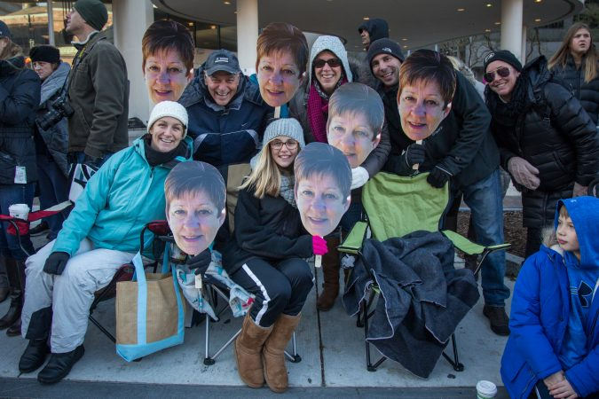 Scott Conaway (top left) holds up a photo of his wife's face with his family. Ingrid Conaway finds the parade too cold, so this year the family brought her in spirit. (Emily Cohen for WHYY)
