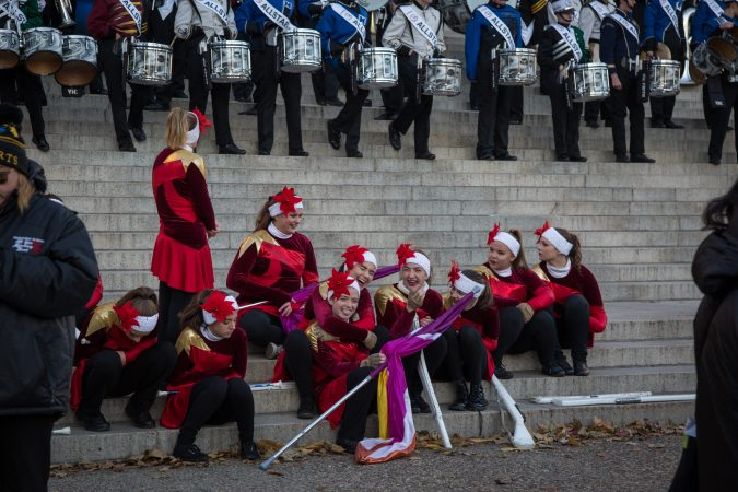 The girls of the AllStars color gaurd have a laugh as they try to stay warm before the start of the 98th annual Philadelphia Thanksgiving Day Parade, November 23, 2017. (Emily Cohen for WHYY)