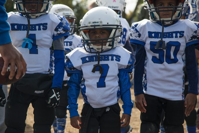 Zaid Duncan, 4, center, lines up to start his football game.