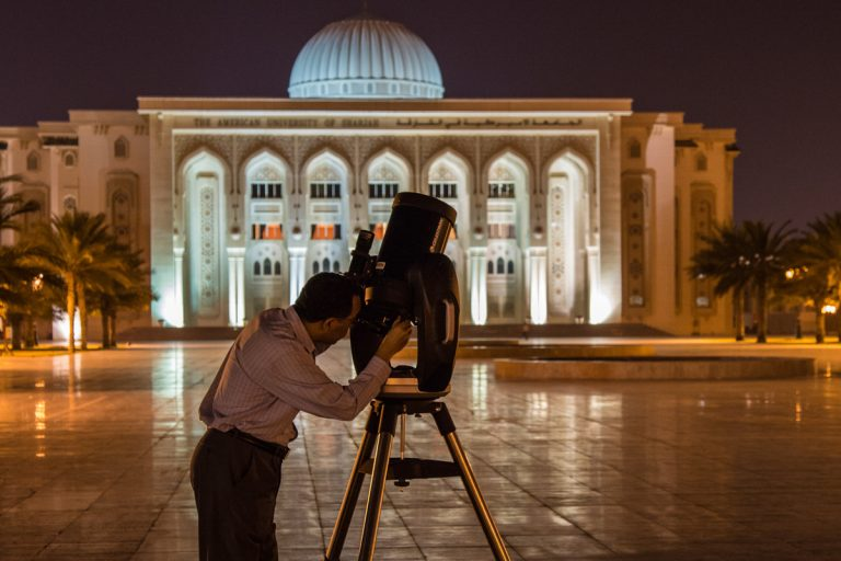 man looking through telescope in Middle East
