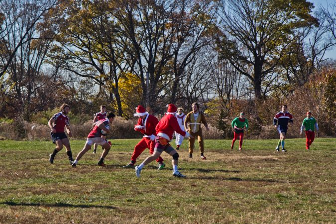 Prep 14 battle the Sexy Santas at the Apple Pie 7s Rugby Tournament in Fairmount Park. (Kimberly Paynter/WHYY)