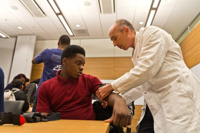 Trauma surgeon Jeremy Cannon, M.D., demonstrates how to put a tourniquet on Sayre 11th grade student, Jahaad Olaore. (Kimberly Paynter/WHYY)