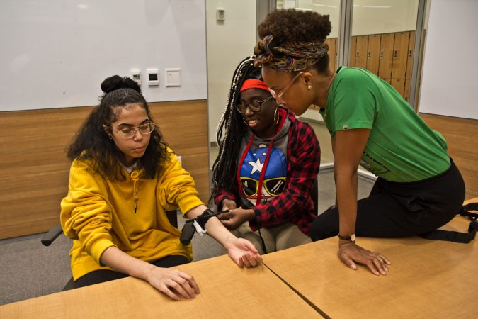 Medical student Camille McCallister supervises Syre students Nydia Henry (right) putting a tourniquet on Danny Miles (left). (Kimberly Paynter/WHYY)