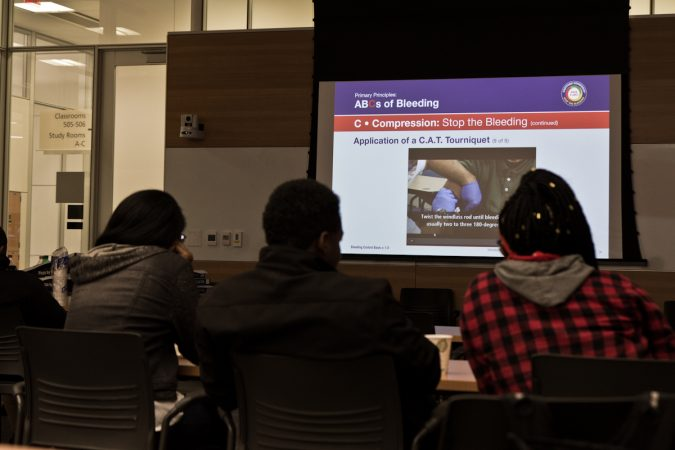 Students from the Sayre, West Philadelphia, and The U School learn about wound care at a Stop The Bleed training. (Kimberly Paynter/WHYY)