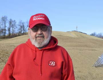 Washington County resident Frank Brownlee stands in his backyard, where a rig on the hill behind him is drilling natural gas wells. (Amy Sisk/StateImpact Pennsylvania)