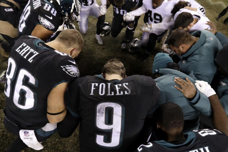 Philadelphia Eagles' Nick Foles (9) kneels with other players after an NFL football game against the Oakland Raiders