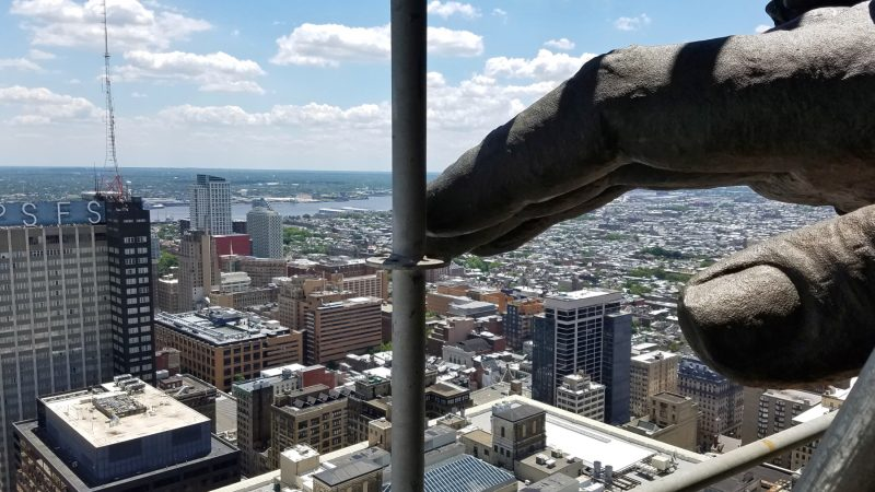 The hand of William Penn hovers above Philadelphia, a view made possible by scaffolding that has been erected to clean and repair the statue atop City Hall. (Peter Crimmins/WHYY)