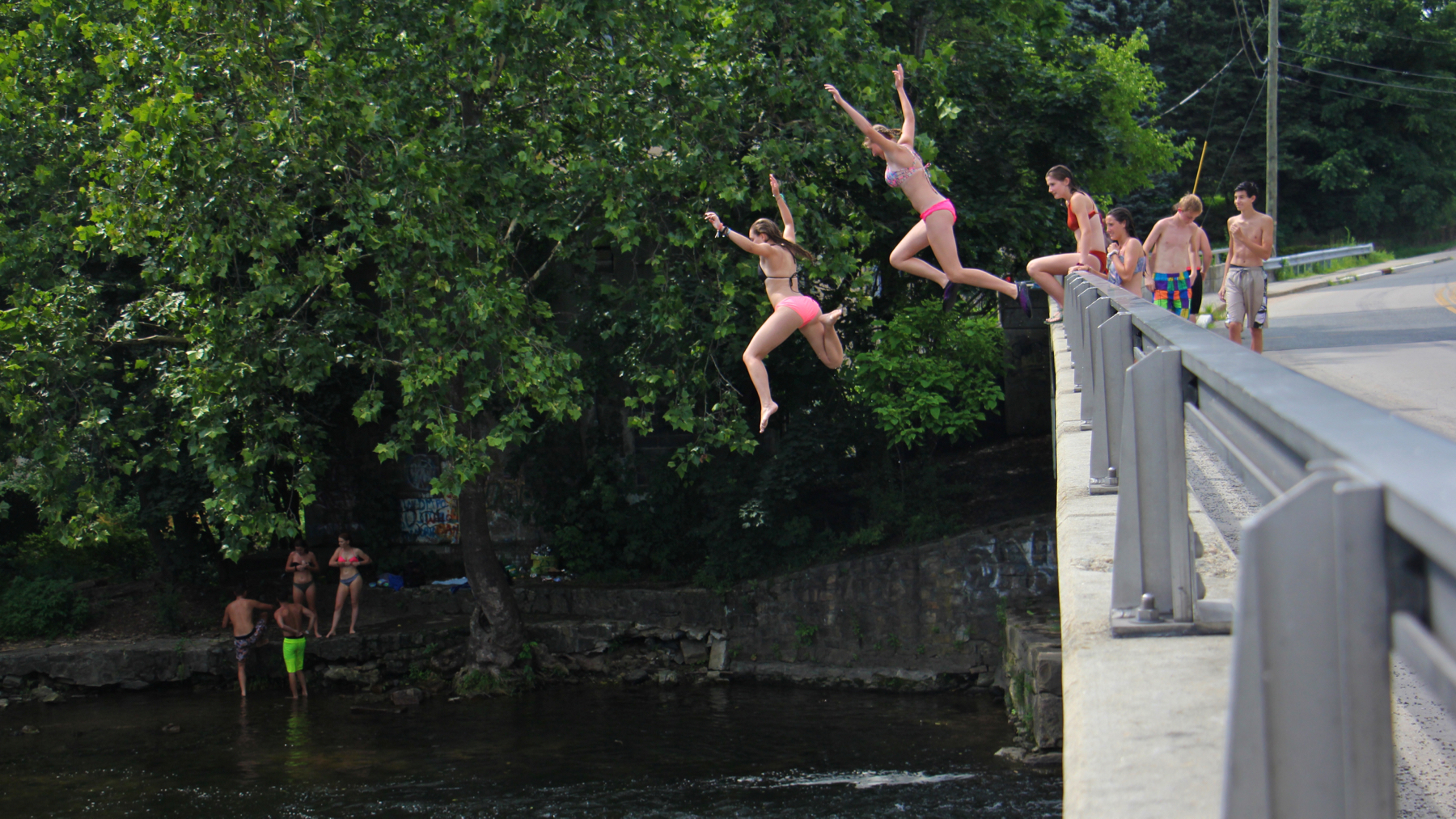Teenagers take turns jumping into the Musconetcong river just below the Asbury Mill Dam.