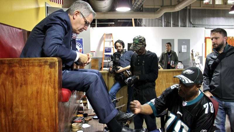 District attorney candidate Larry Krasner (left) stops for a shoe shine at Reading Terminal Market while campaigning on the eve of the 2017 election. (Emma Lee/WHYY)