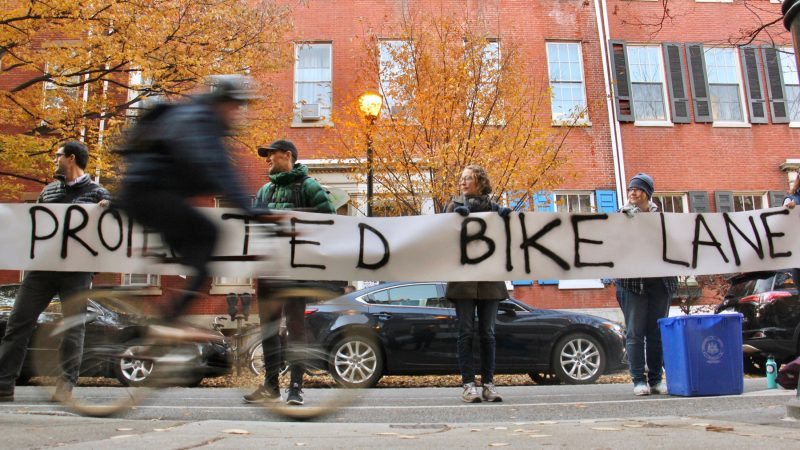 Protesters demanding protected bike lanes form a human barrier stretching for two blocks along Spruce Street near 11th Street, where a cyclist was killed by a garbage truck the previous morning. (Emma Lee/WHYY)
