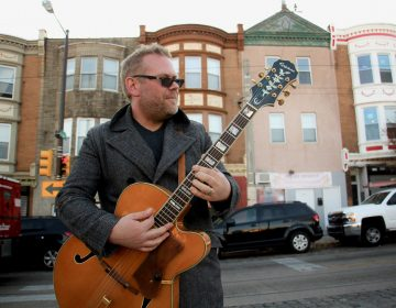 Colton Weatherston plays his guitar in front of colorful building facades on Germantown Avenue