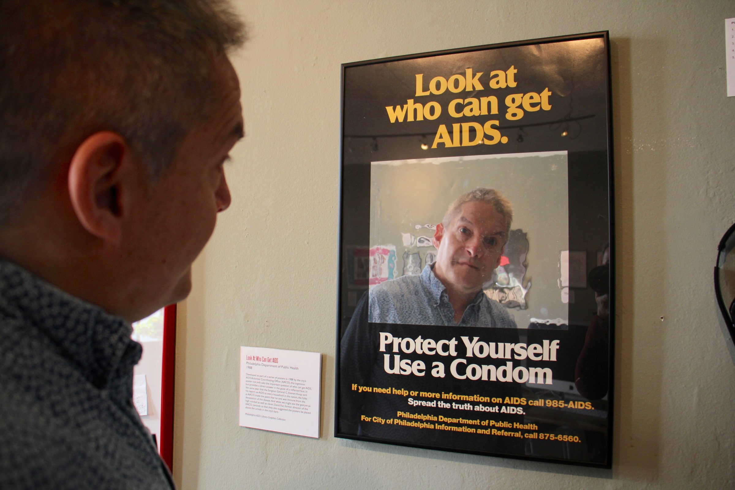 Christopher Bartlett, executive director of the William Way LGBT Center. gazes omtp the reflective surface of a 1988 AIDS awaremess poster.
