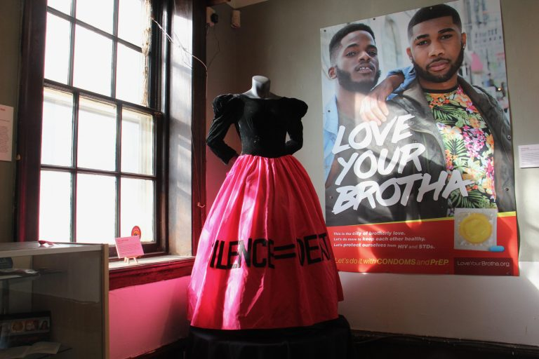 The SILENCE=DEATH gown worn by activist Dominic Bash stands beside a 2017 poster in the William Way exhibit documenting Philadelphia's battle against AIDS