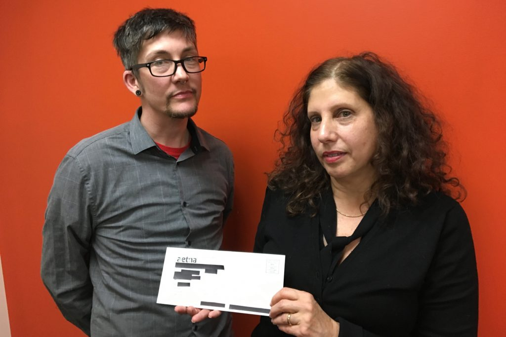Adrian Lowe (left), staff attorney with Aids Law Project and Ronda Goldfein, attorney and executive director of the Aids Law Project, hold a letter that was sent to thousands of Aetna members, revealing their HIV positive status through an over-large mailing window.