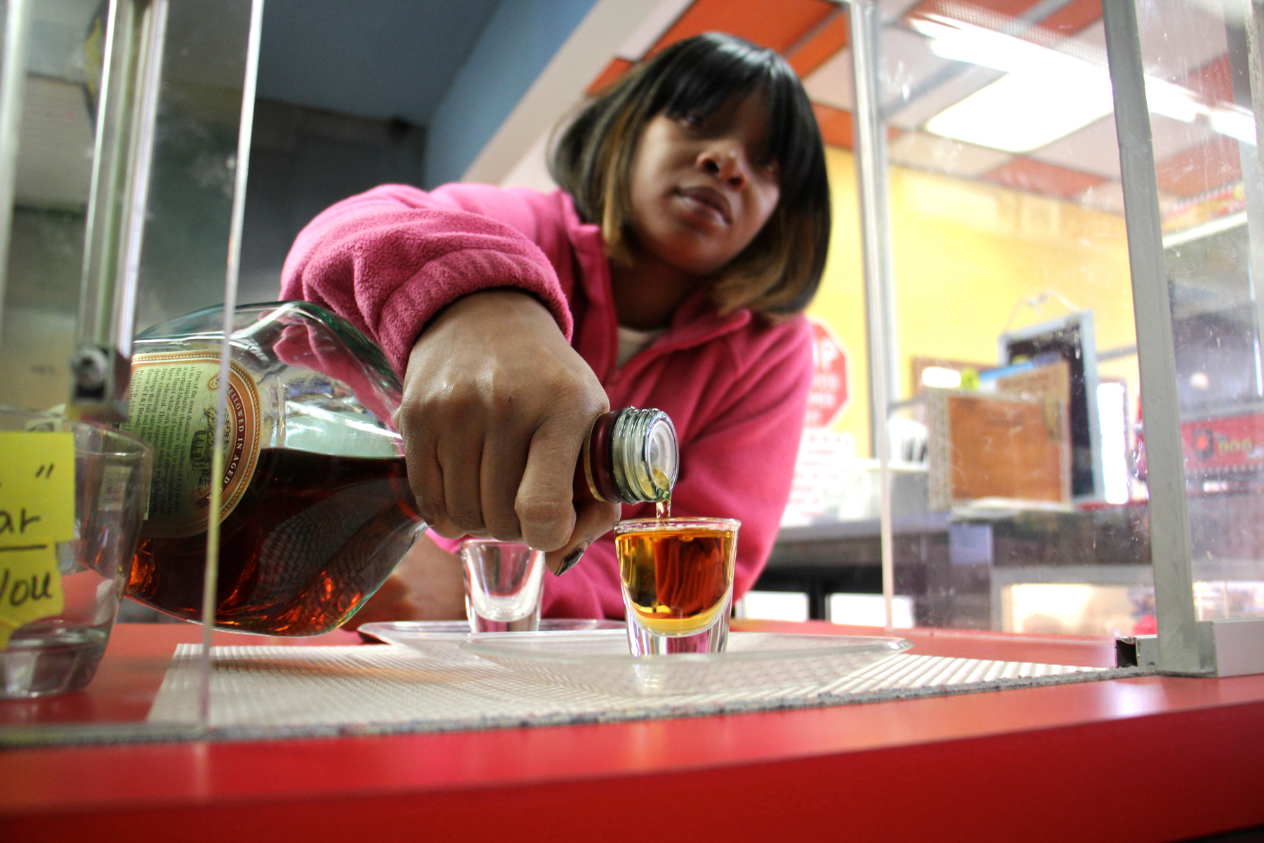 After opening a sliding plexiglass door, Nasifa Erwin pours a shot for a customer at Olney Steak and Beer on North Broad Street.