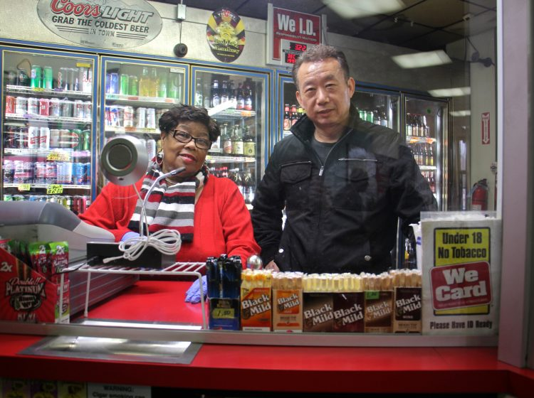 Olney Steak and Beer owner O. J. Yoo stands behind a plexiglass window with employee Sylvia Combs.