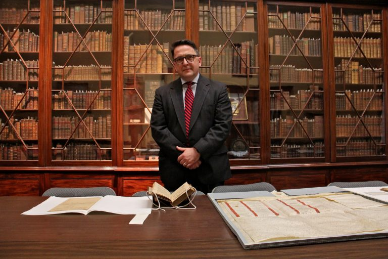 Michael Barsanti, director of the Library Company of Philadelphia, stands before a glass fronted bookcase