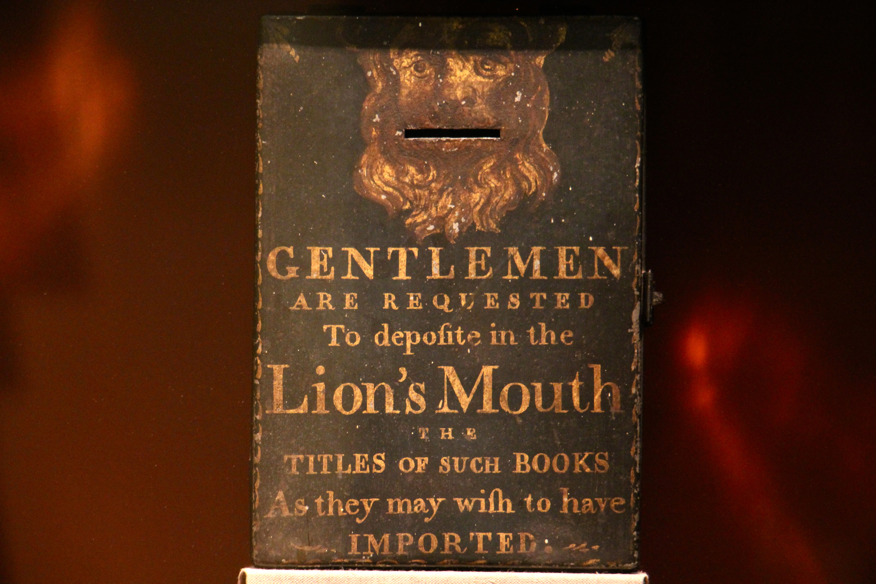 A relic from the early days of Benjamin Franklin's Library Company , a box for requested titles, remains on the shelf behind a layer of plexiglass.