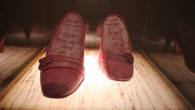 The shoes of Ortiz's grandmother are inscribed with a poem and the signature from her Colombian passport. (Emma Lee/WHYY)